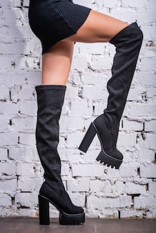 Black hessian boots on the feet of a model on a white brick background