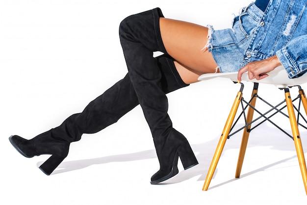 白い背景の上のモデルの脚に黒いヘシアンブーツ