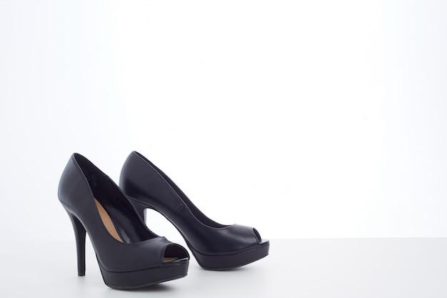 Черные туфли на высоком каблуке на белом