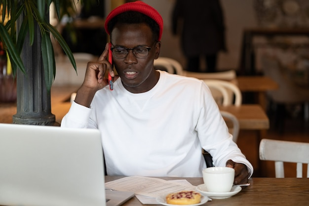 Black hipster man talking on mobile phone remotely online work on laptop in cafe holding cup of tea