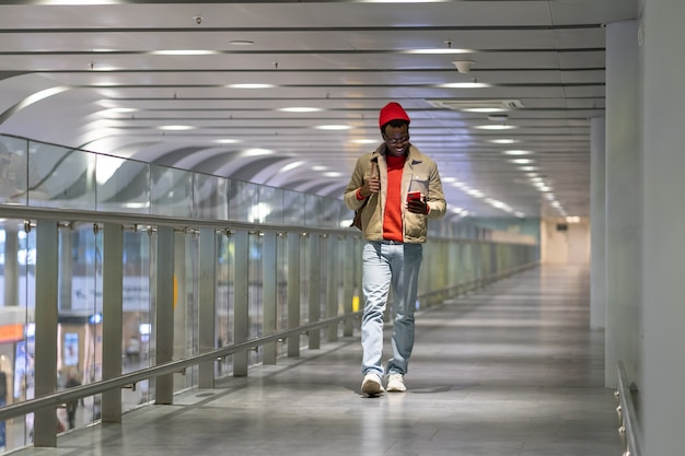 Black hipster millennial man walking in airport terminal using cellphone chatting in social networks