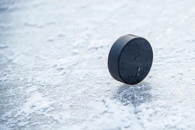 Black hockey puck lies on ice at stadium