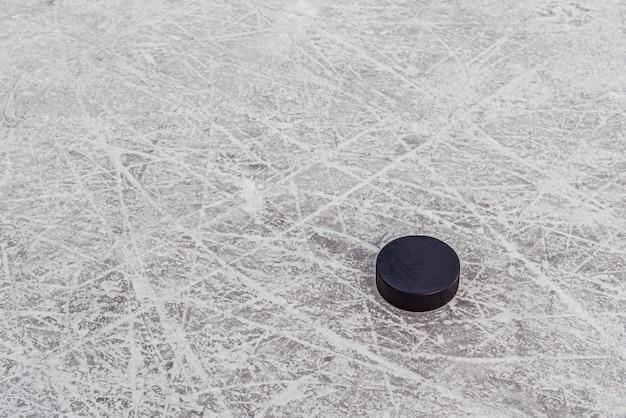 Черная хоккейная шайба лежит на льду на стадионе