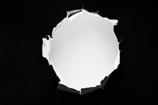 Черная дыра в бумаге с рваными сторонами.