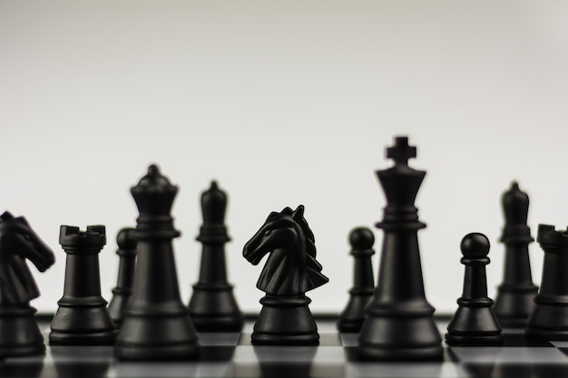 Black horse chess figures on board.- business idea for competition.