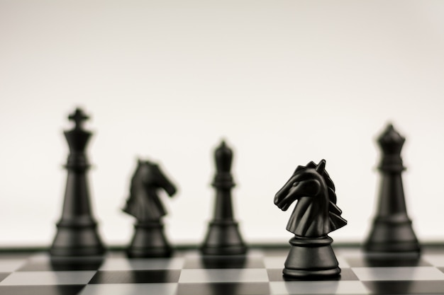 Black horse chess stand alone on a chessboard. - business winner and fight concept.