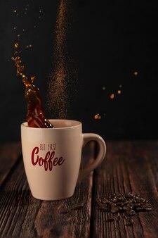 Черный горячий кофе плещется в бежевой чашке и порошок корицы падает на темный деревянный стол с фасолью