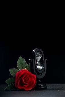 Черные песочные часы с красным цветком как память на темной поверхности
