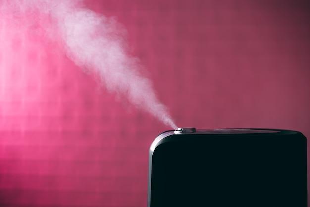 白い蒸気とピンクの背景に黒の加湿器