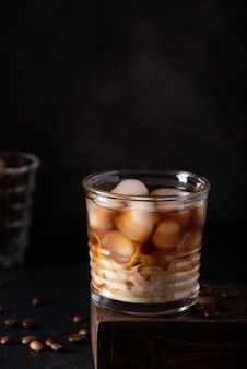 Black ice coffee with milk in a glass on a black background