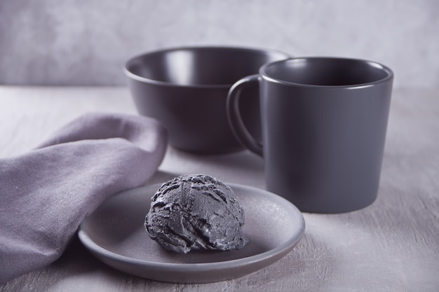 Black ice cream on a black ceramic plate with gray napkin on a gray table