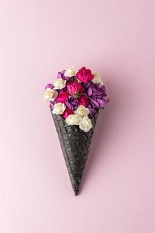 Черный рожок мороженого с яркими цветами на пастельно-розовом