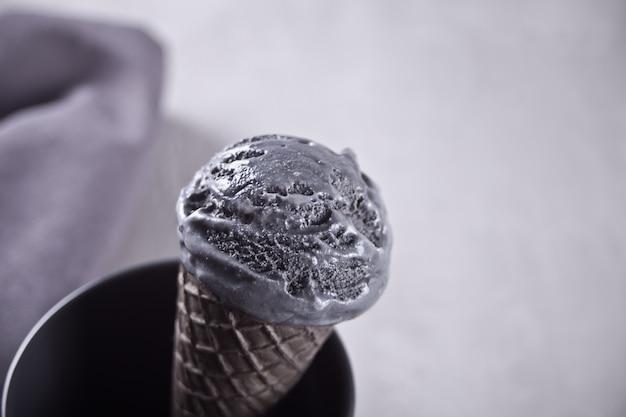 Black ice cream in traditional portioned ice cream cones.