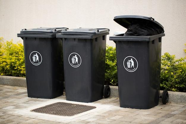 リサイクルおよびゴミ用の黒い屋内廃棄物コンテナ。外の多くの閉じたリサイクルゴミ箱
