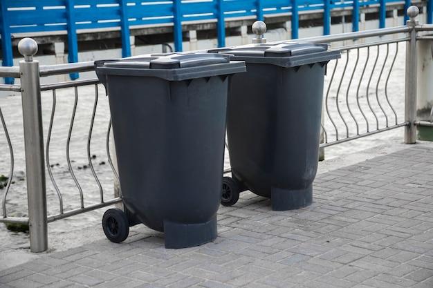 Черные внутренние мусорные контейнеры для утилизации на тротуаре. закрытые и перерабатываемые емкости мусорное ведро снаружи