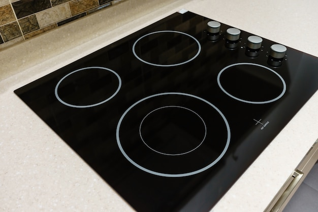 Black induction stove, cooker, hob or built in cooktop with ceramic top in white kitchen