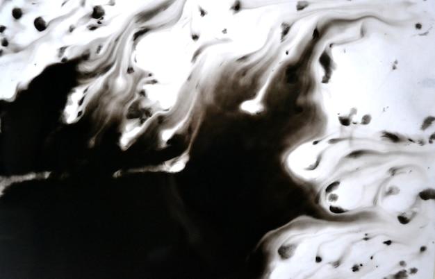 白いクローズアップ紙の上に運ばれた黒いインク。白い背景で隔離の抽象的な背景。インクの汚れが広がり、紙のマクロに吸収されます。