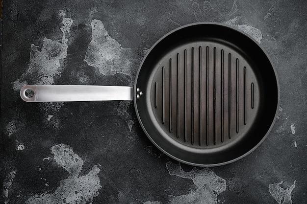 Черная железная пустая сковорода для гриля с копией пространства для текста или еды с копией пространства для текста или еды, плоская планировка, вид сверху, на черном фоне темного каменного стола