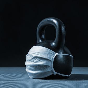 검은 바탕에 수술용 마스크가 있는 검은 철 케틀벨. 코로나바이러스로 인해 폐쇄된 체육관
