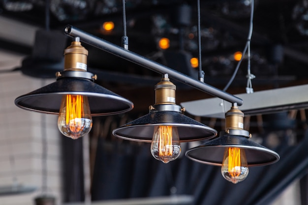Black iron loft chandeliers with edison lamps on a black background, bokeh.
