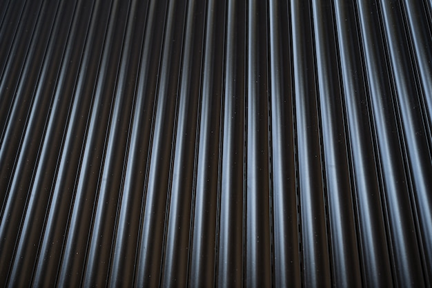 Black iron tin fence lined background. metal texture