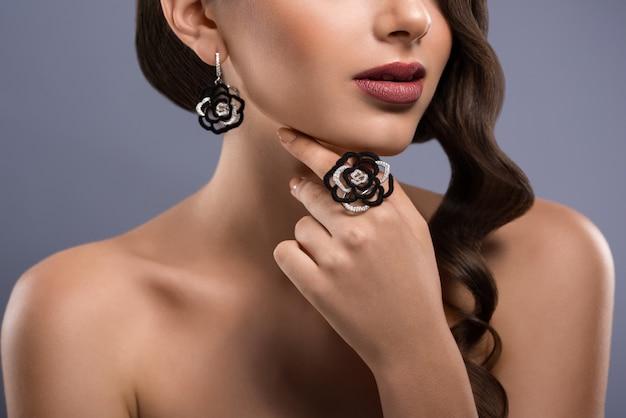 黒は永遠の定番です。花形のリングと黒と白の宝石のイヤリングを身に着けている女性モデルのトリミングされたクローズアップ