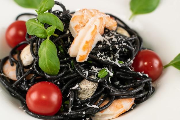 白いレストランのプレートにエビ、チェリートマト、グリーンを添えた黒のイタリアンシーフードパスタ。黒の自家製スパゲッティ、イカ墨入りヌードル、調理済みシーフードマカロニクローズアップ