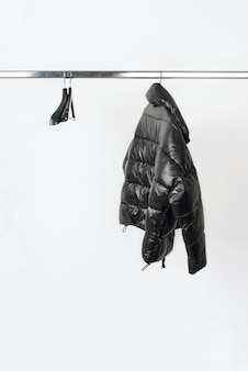 흰색 배경에 고립 된 옷걸이에 검은 자 켓 최소한의 패션 의류 개념