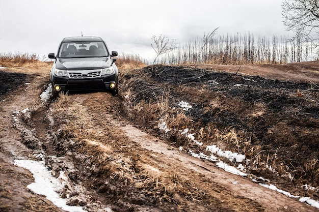 深い泥のある未舗装の道路での黒い日本のクロスオーバー