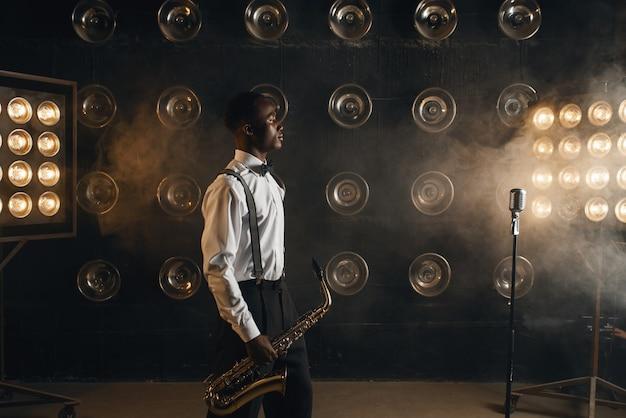 煙のステージでサックスを持つ黒人のジャズ ミュージシャン。楽器を手に持つ黒人のジャズマン