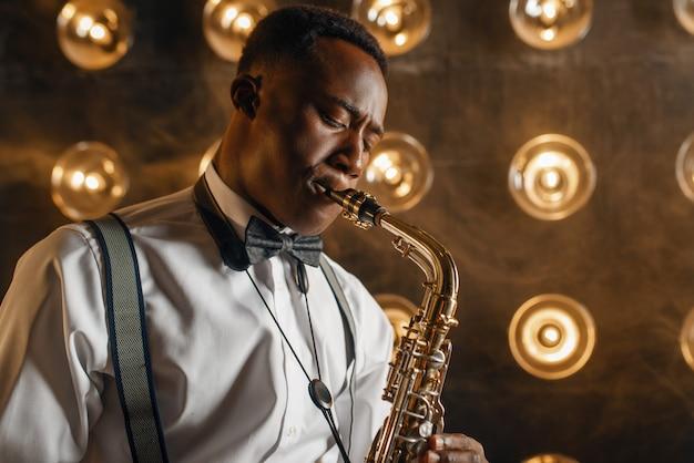 Черный джазовый исполнитель играет на саксофоне на сцене