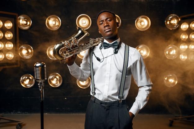 Черный джазовый исполнитель позирует с саксофоном на сцене