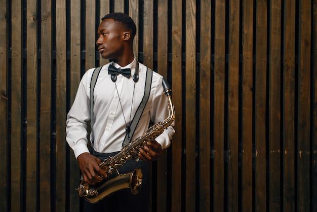 Черный джазовый исполнитель с саксофоном. черный джазмен преформирует на сцене