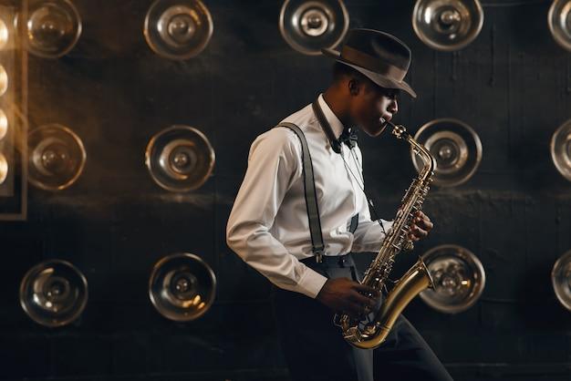 帽子をかぶった黒いジャズマンが、スポット ライトを当ててステージでサックスを演奏します。現場で活躍する黒人ジャズ ミュージシャン