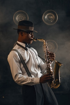 ブラック ジャズマンは、スポット ライトでステージでサックスを演奏します。現場で活躍する黒人ジャズ ミュージシャン