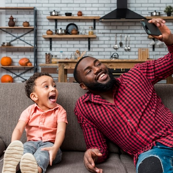 Black joyful father and son taking selfie