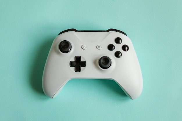 Black joystick gamepad, game console isolated on pastel blue colourful trendy .