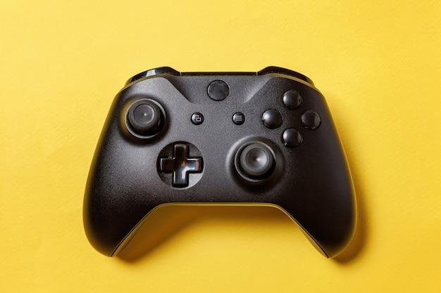 Черный джойстик геймпад, игровая консоль на желтом красочном фоне