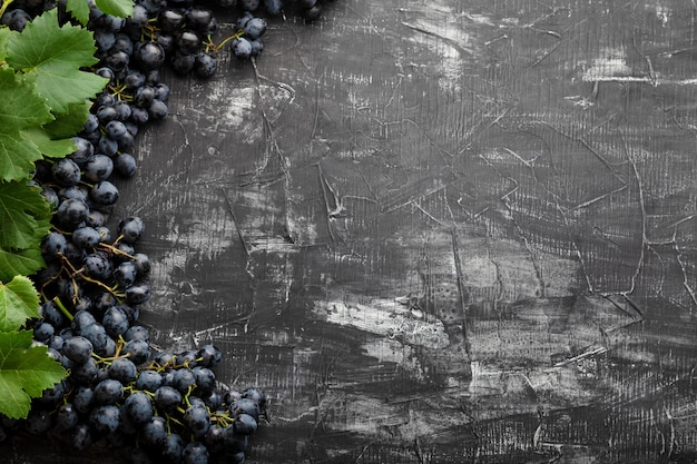 Black juicy grapes on vintage dark concrete background. frame made of grapes. copy space for text or menu on black scuffed background. frame made of grape fruits with place for text on dark background