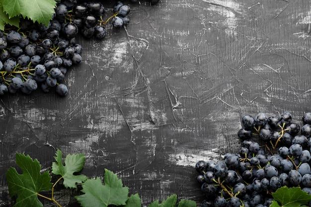 Black juicy grapes on vintage dark concrete background frame made of grapes