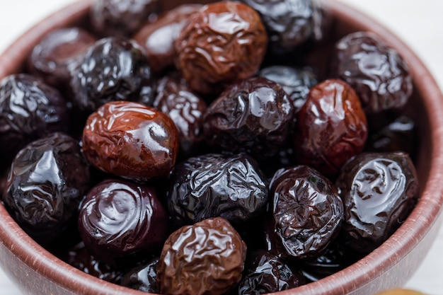 Black and kalamata olives in a clay bowl on white. close-up.
