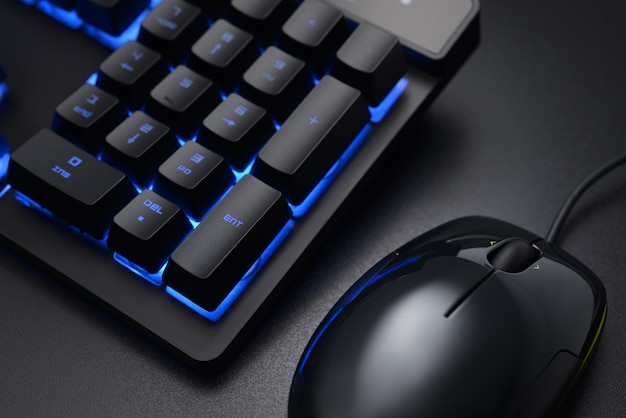 Черные цифровые клавиши клавиатуры и проводная мышь на темном офисном столе