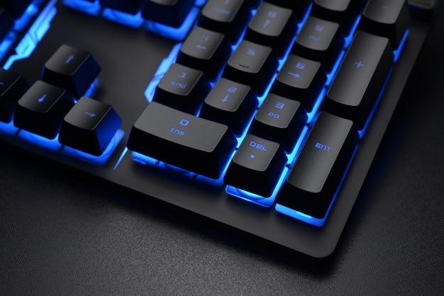 暗いオフィスの机の上の黒いキーボード