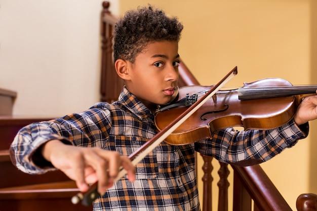 Черный парень играет на скрипке мальчик играет на скрипке на высоких нотах лестницы и красиво звучит юных скрипачей ...