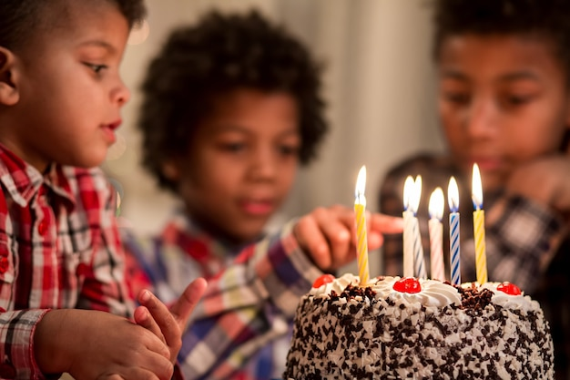 Black kid touching cakes candle boy touches birthday cakes candle be careful my friend dont play wit...