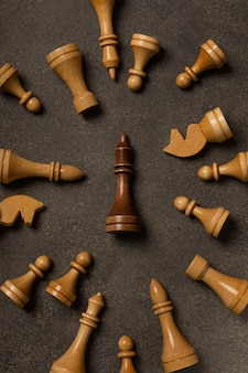 Black king among white chess pieces on dark background