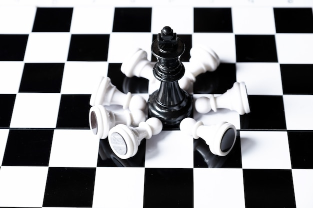 Black king chess on board with white chesses army leader challenges planning business strategy