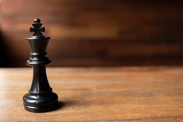 Black king chess on wooden background leader challenge planning business strategy to success concept