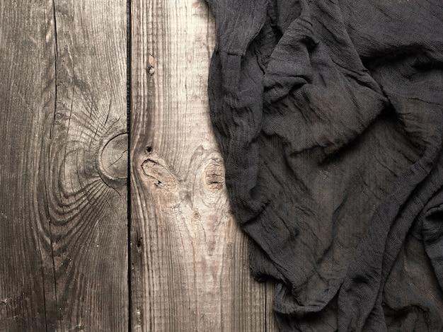 灰色の木製テーブルに折りたたまれた黒いキッチンテキスタイルタオル