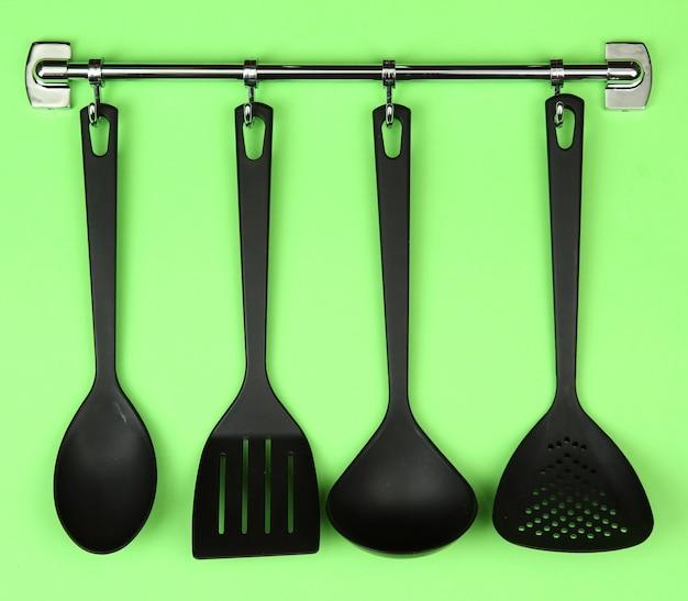 Black kitchen utensils on silver hooks, on green surface